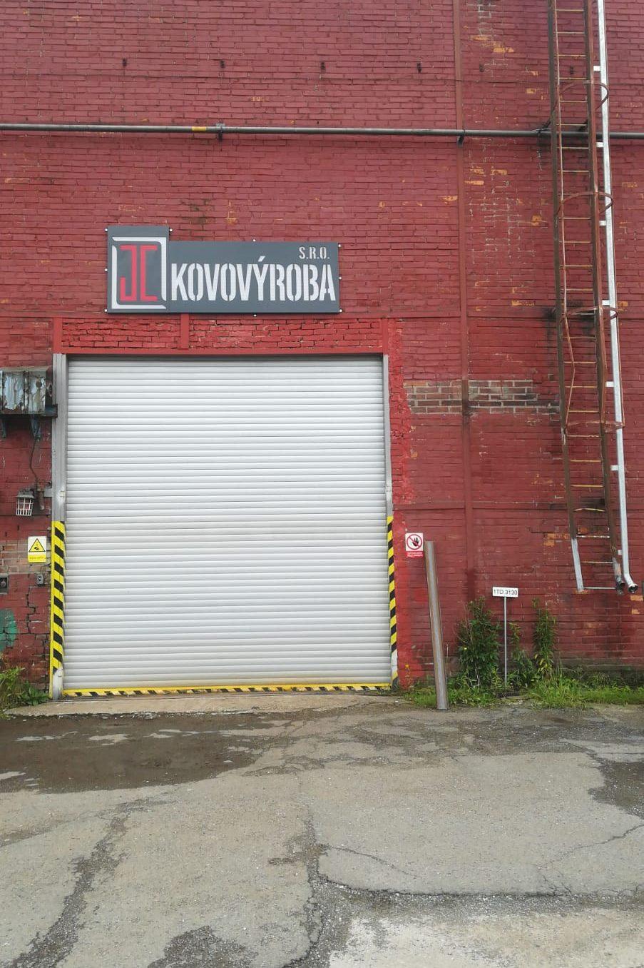 Nové logo nad bránou vedoucí do dílny